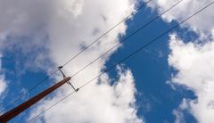 Single wooden electricity pole with three cables carrying electric supply to  Stock Photos