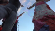 Happy kids jumping to touch floating soap bubbles, summer evenning, slow 1 Stock Footage