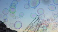 Many soap bubbles floating on blue sky - public square, summer evenning - slow 1 Stock Footage