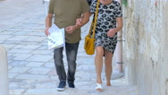 Married couple of tourists walking down an old town checking the map Stock Footage