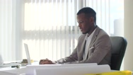 Black young businessman using laptop computer sitting in a modern white office Stock Footage
