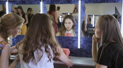 Three girls sit in front of mirror and happily talk with each other Stock Footage