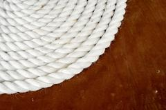 Single coil of white rope stacked in a circle set against a dark brown wood b Stock Photos