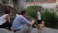 Little Girl Plays With a Small Dog Near to River Stock Footage