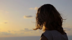 Lonely young woman looking out to sea at sunset as the wind moves the hair Stock Footage