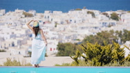 Beautiful young woman relaxing near pool with amazing view on Mykonos, Greece Stock Footage