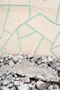 Broken rubble in chunks set against a crazy paving tiled wall Stock Photos
