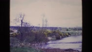 1969: a man standing in a beautiful river fly fishing ENGLAND Stock Footage
