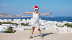 Little funny girl in red Santa hat outdoors background of Mykonos. Kid at street Stock Footage