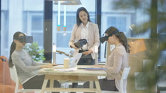 4K Businesswomen in young creative company trying out virtual reality viewers Stock Footage