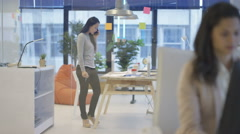 4K Attractive businesswoman in creative office talking on phone & brainstorming Stock Footage