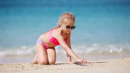Little girl drawing pictures on sandy beach Stock Footage