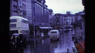 1969: a busy, wet city street with traffic and a double-decker bus ENGLAND Stock Footage