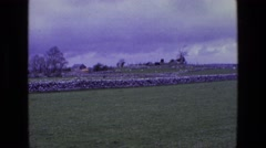 1969: a beautiful stone fence with a grassy foreground and a cloudy dark sky Stock Footage