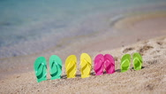 Family flip flops on beach in front of the sea Stock Footage