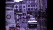 1969: cars and pedestrians moving through the wet road in a busy city IRELAND Stock Footage