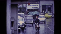 1969: a city urban street wet with rain, featuring a man on a motorbike IRELAND Stock Footage
