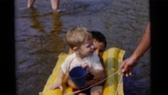 1963: brothers floating on a plastic floater pulled by dad on the beach CAMDEN Stock Footage