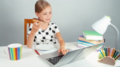 School girl typing something in her laptop and eating donut sitting at the desk Stock Footage