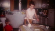Mom cleans kitchen prepares for dinner 3648 vintage film home movie Stock Footage