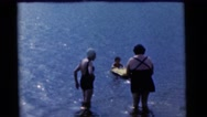 1963: a boy with floating rift in water and watched by two women CAMDEN Stock Footage