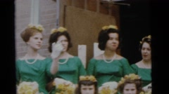 1963: four women in green and four men in black and white standing together Stock Footage