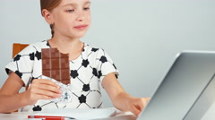 Schoolgirl eating chocolate and typing in her laptop sitting at the desk Stock Footage