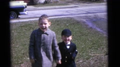 1963: two rambunctious well dressed boys standing on the lawn CAMDEN, NEW JERSEY Stock Footage