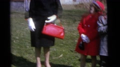 1963: an adult woman, accompanied by two little girls, is standing  Stock Footage