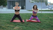 Two girl doing active exercise with smile on the grass in the morning in 4K Stock Footage