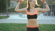 Pretty girl doing active exercises with weights outdoor in 4K Stock Footage