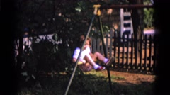 1963: a little lad is showing acrobatics on the pole in the garden CAMDEN Stock Footage