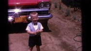 1963: two children laughing while playing in a field against a red wagon CAMDEN Stock Footage