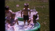 1963: a group of children splashing in a portable pool on a sunny day CAMDEN, Stock Footage