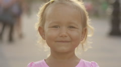 Cute little girl wink to the camera in the public park Stock Footage