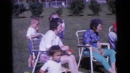 1963: a group of people sitting in a backyard by a sprinkler on a sunny day Stock Footage