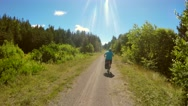 A woman riding a bike through beautiful green forest Stock Footage