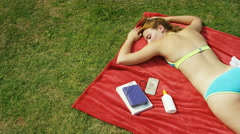 Young woman relaxes in the sunshine on her blanket, with space for text Stock Footage