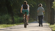 SLOW MOTION: People run and ride in a park Stock Footage