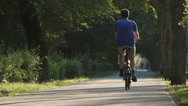 Young man rides in a park (slow motion) Stock Footage