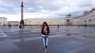 Brunette woman walk over Palace Square, texting on smartphone Stock Footage