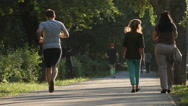 SLOW MOTION: People run and walk in a park Stock Footage