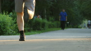 Young man runs in a park - feet level Stock Footage