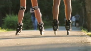 Young couple rollerblades on an alley - feet level (slow motion) Stock Footage