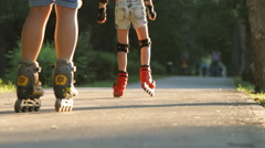 Young family rollerblades on an alley - feet level (slow motion) Stock Footage