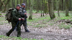 Two men in uniform with backpacks and sticks for walking go along the forest Stock Footage