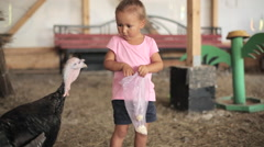 Little girl feeding a hen in hen farm and scared turkey Stock Footage