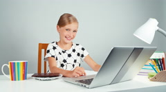 Schoolgirl holds chocolate and gives you it at camera sitting at the desk Stock Footage