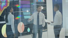 4K Business team in modern office, looking at video wall with graphs & data Stock Footage