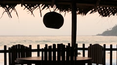 Table and lamp in a tropical cafe on the beach at sunset Stock Footage